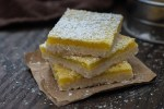 Three lemon bars stacked on top of each other sprinkled with powdered sugar sitting on a piece of brown paper on a wooden surface