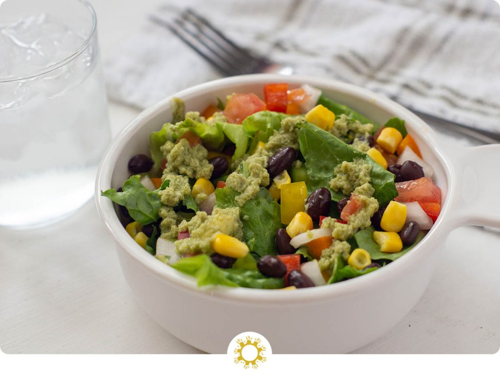 Southwestern salad with an avocado dressing in a white round bowl with a stainless steel fork and glass of water behind (with logo overlay)