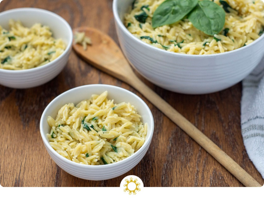 Cheesy Spinach Orzo Pasta Sides in a small white bowl next to a wooden spoon with two more bowls in the background all on a wooden surface (with logo overlay)