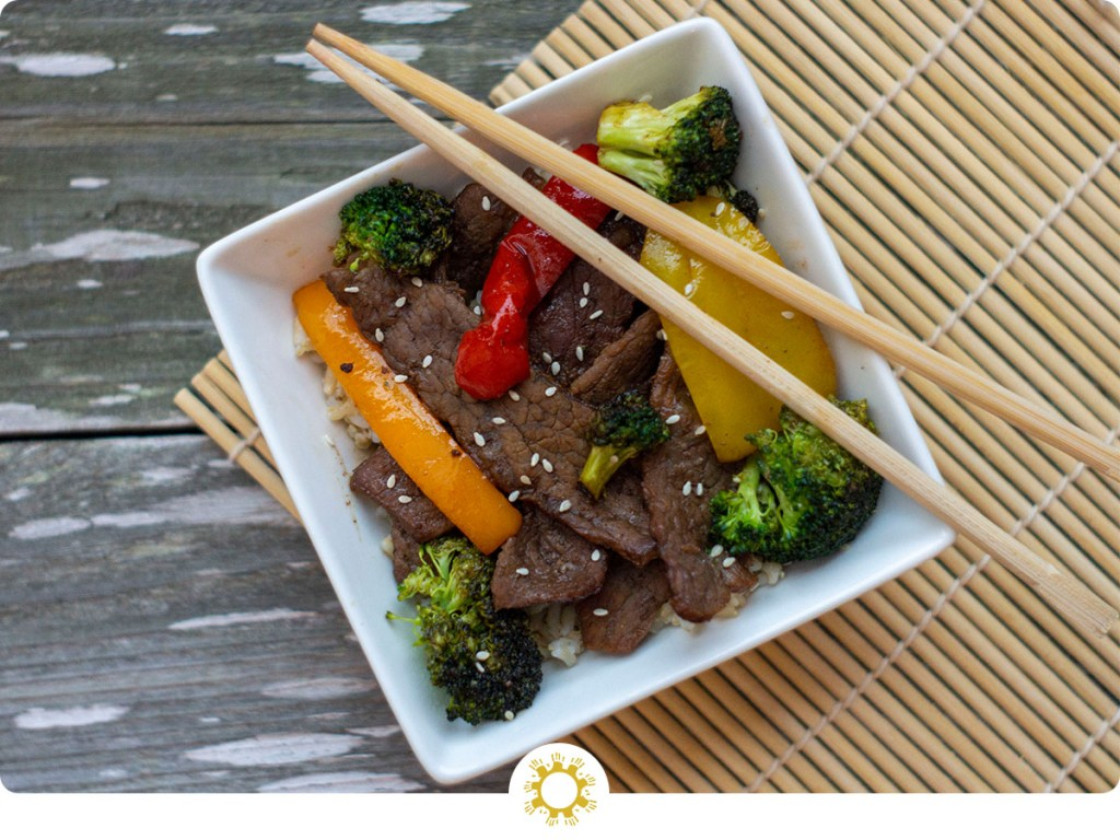 Top-down of Mongolian Beef Stir-Fry in a square white bowl with chop sticks on a wooden surface with a bamboo placemat (with logo overlay)