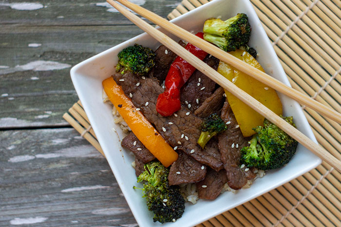 Top-down of Mongolian Beef Stir-Fry in a square white bowl with chop sticks on a wooden surface with a bamboo placemat