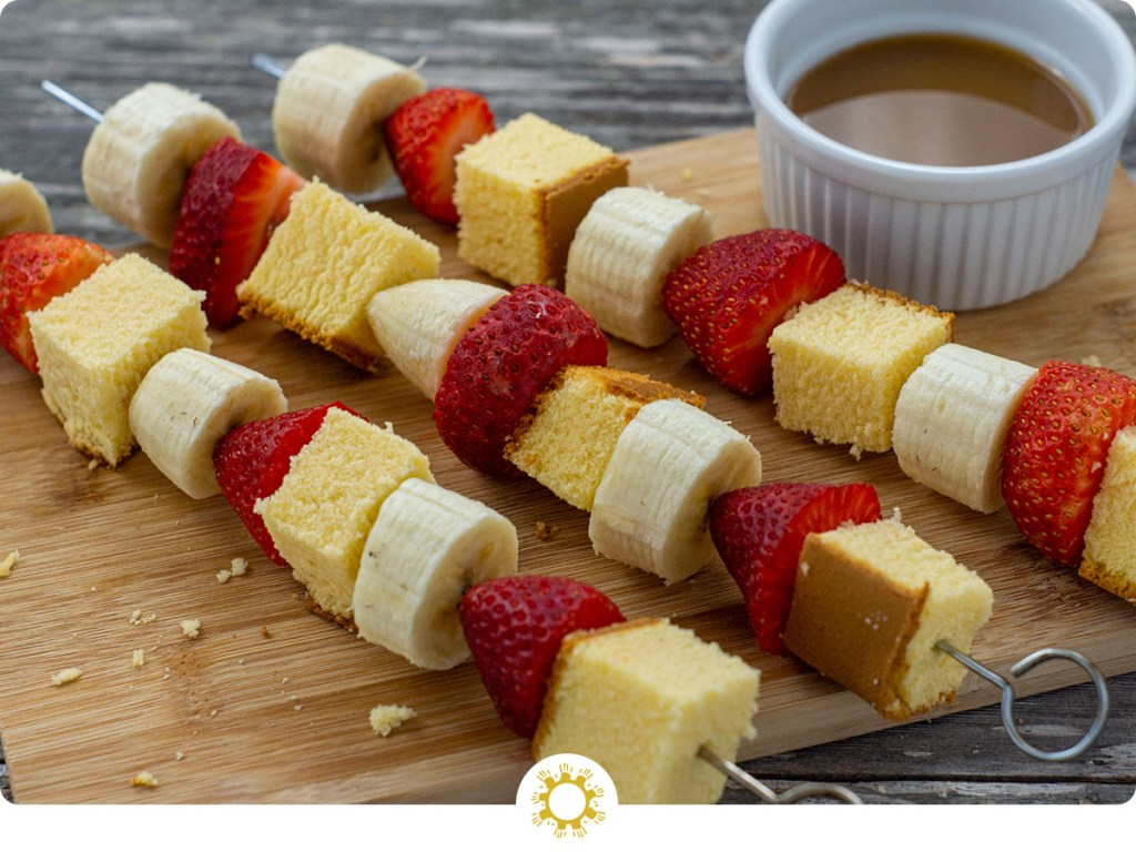 Fruit kabobs with alternating pound cake, strawberries, and bananas on metal skewers on a bamboo board with a white dish of caramel dipping sauce behind all on a wooden surface (with logo overlay)
