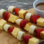 Fruit kabobs with alternating pound cake, strawberries, and bananas on metal skewers on a bamboo board with a white dish of caramel dipping sauce behind all on a wooden surface (vertical with title overlay)