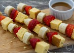 Fruit kabobs with alternating pound cake, strawberries, and bananas on metal skewers on a bamboo board with a white dish of caramel dipping sauce behind all on a wooden surface