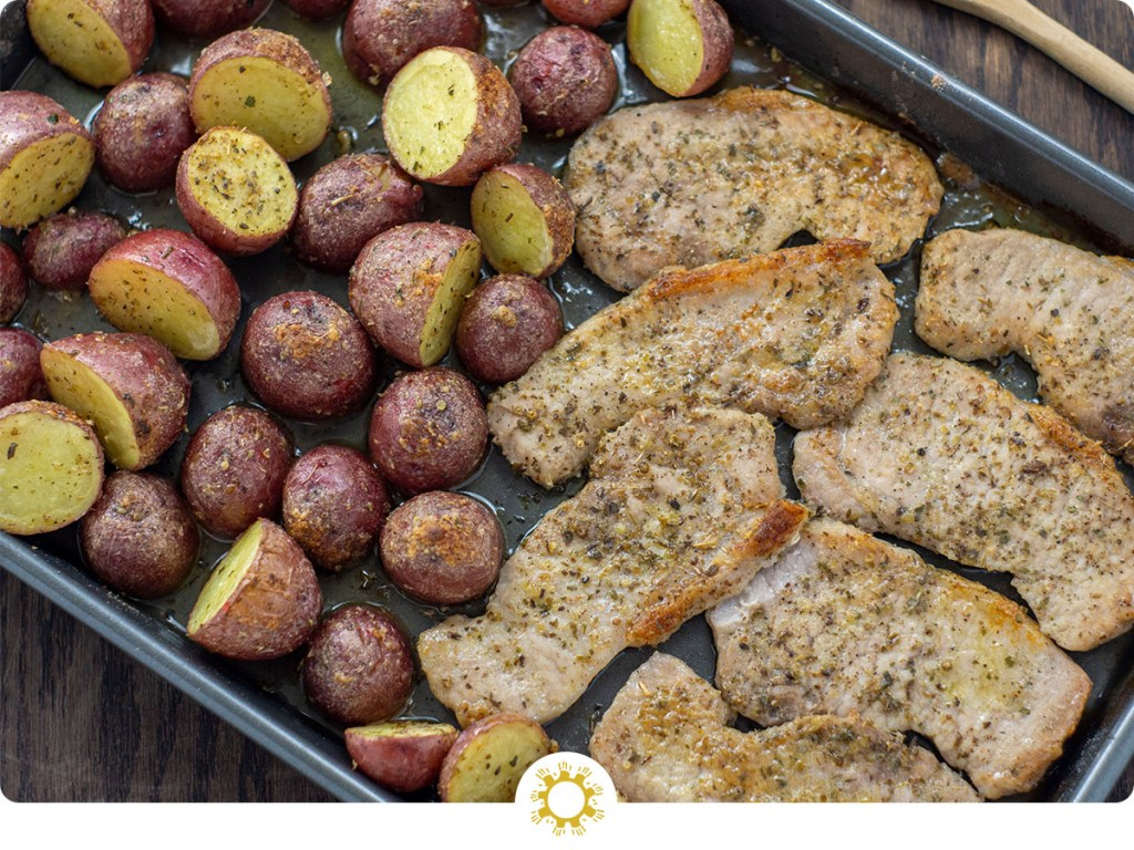 Cooked potatoes and ranch pork on a metal sheet pan next to a wooden spoon on a wooden surface (with logo overlay)