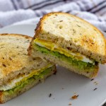 Avocado egg toast of toasted bread with fried egg and smashed avocado as a sandwich sliced in half of a white plate with a white and brown towel behind all on a wooden surface (vertical with title overlay)