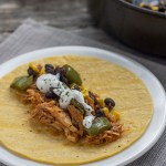 BBQ chicken and black bean taco fillings on a corn tortilla on a round white plate on a grey placemat next to a nonstick skillet with taco fillings all on a wooden surface
