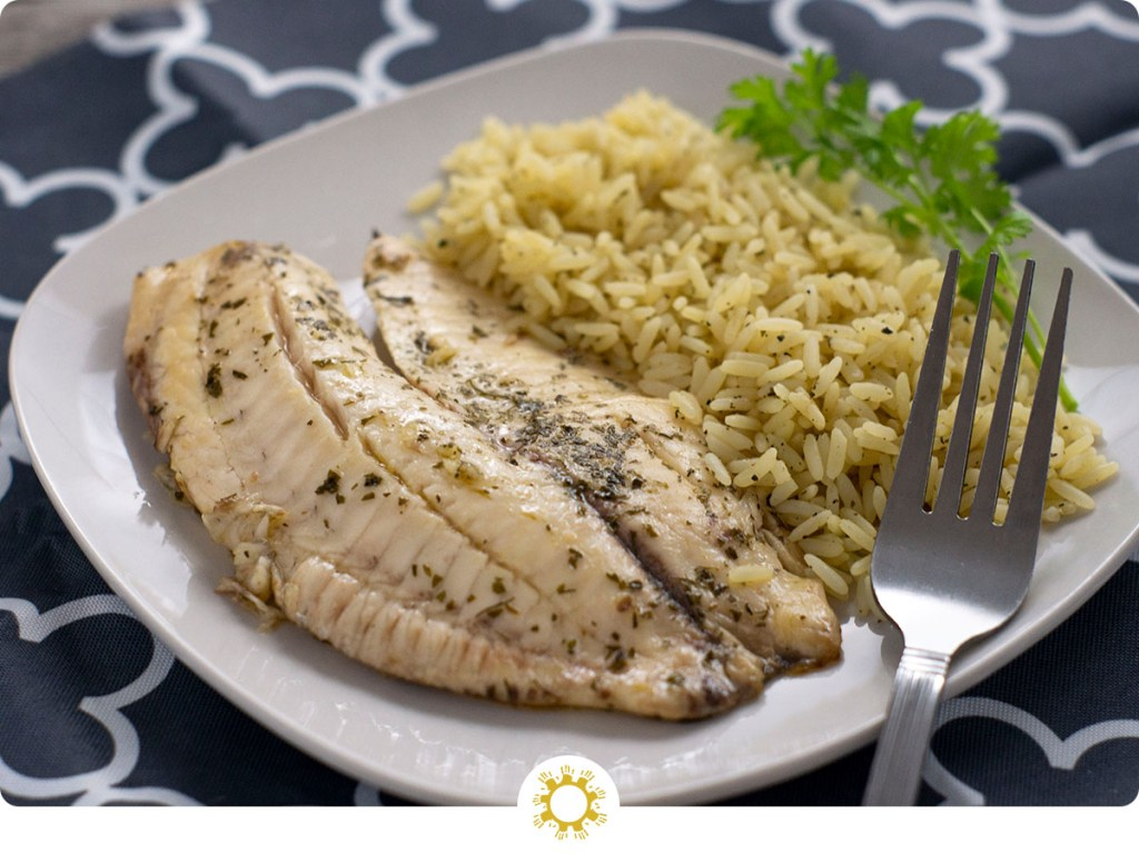 Cilantro and lime juice covered fish fillets next to cilantro lime rice with a sprig of fresh cilantro on a square white plate with a stainless steel fork on a white and grey placemat on a wooden surface (with logo overlay)