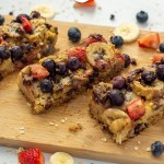 3 sliced oatmeal bars on a bamboo cutting board with extra fruit around the edge (with title overlay)