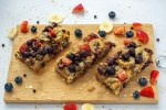 3 sliced oatmeal bars on a bamboo cutting board with extra fruit around the edge