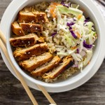 Sweet and sour chicken in rice with a scoop of coleslaw in a white round bowl on top of a white round plate with bamboo chopsticks on the plate and a white and brown towel behind all on a wooden surface (vertical with title overlay)