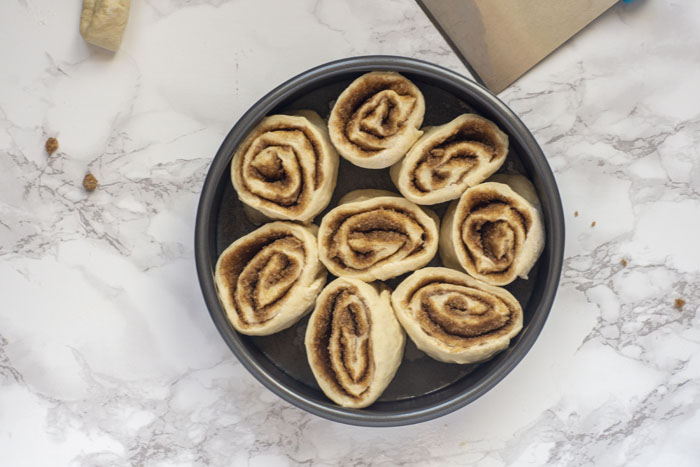 Cut cinnamon rolls laying on their sides so the roll is facing upwards in a round 9-inch metal cake pan next to a pastry cutter and extra bit of dough on a white and grey marble surface