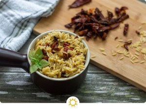 Sun-Dried Tomatoes with Basil in Orzo Pasta in a small brown dish with extra ingredients in the background (with logo overlay)