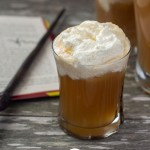 Glass of Butterbeer topped with whipped topping next to an open book and a magic wand with a pitcher of Butterbeer in the background all on a wooden surface (vertical with title overlay)