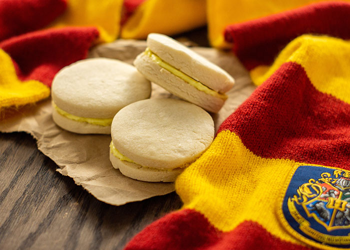 3 Canary Creams on a piece of brown butcher paper surrounded by a Gryffindor scarf on a wooden surface