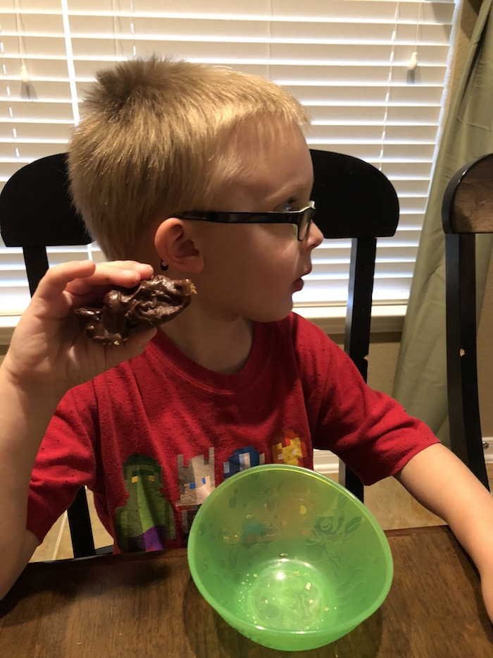 Young boy looking to the side sitting at a table with a Cockroach Cluster dessert in his hand with a green bowl in front of him