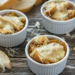3 small white ramekins with cooked french onion soup on a wooden surface with shredded cheese and chunks of bread around them with sliced bread and a towel in the background