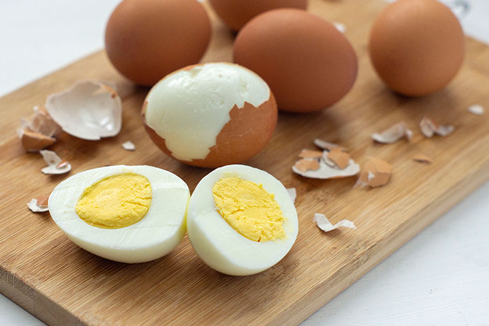 Hard-boiled egg sliced in half on a wooden cutting board next to shell pieces and other eggs