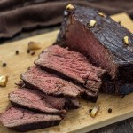 Roast beef on a bamboo surface with a few slices laid over with peppercorn around it in front of a brown towel all on a wooden surface