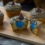 Sorting hat cupcakes with one cut in half showing blue frosting inside on a bamboo board with the sorting hat behind and a magic wand in front all on a wooden surface (vertical with title overlay)