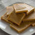 Treacle fudge piled on a white plate on top of a tan placemat on a wooden surface (vertical with title overlay)