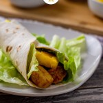 Hawaiian chicken wraps filled with bbq chicken, pineapple chunks, and lettuce in a flour tortilla over a bed of lettuce on a square white plate with a bamboo platter behind with round white bowls of cheese, lettuce, and pineapple all on a wooden surface (vertical with title overlay)