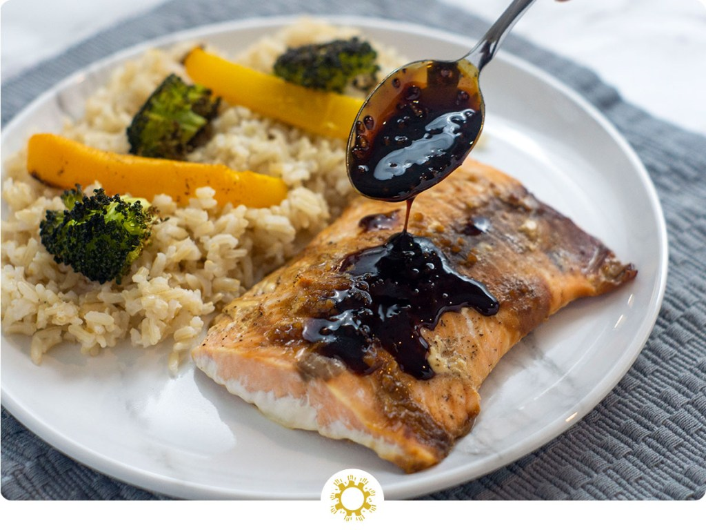 Woman's hand holding a spoon with soy-molasses glaze dripping onto a fillet of cooked salmon next to a bed of rice with roasted yellow bell pepper and broccoli on a round white and grey marbled plate on top of a grey placemat on a white and grey marbled surface (with logo overlay)