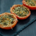 Three Cheesy Caper-Stuffed Tomatoes on a slate serving dish on a dark wooden surface (vertical with title overlay)