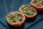 Three Cheesy Caper-Stuffed Tomatoes on a slate serving dish on a dark wooden surface
