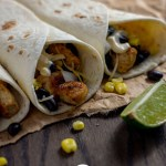 Three chipotle chicken tacos with a few ingredients falling out on a piece of brown parchment paper next to a lime wedge on a wooden surface (vertical with title overlay)