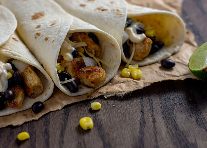 Three chipotle chicken tacos with a few ingredients falling out on a piece of brown parchment paper next to a lime wedge on a wooden surface