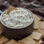 Hot Virginia Dip in a brown dish with crackers around the bowl and a brown towel in the background (vertical with title overlay)