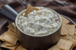 Hot Virginia Dip in a brown dish with crackers around the bowl and a brown towel in the background