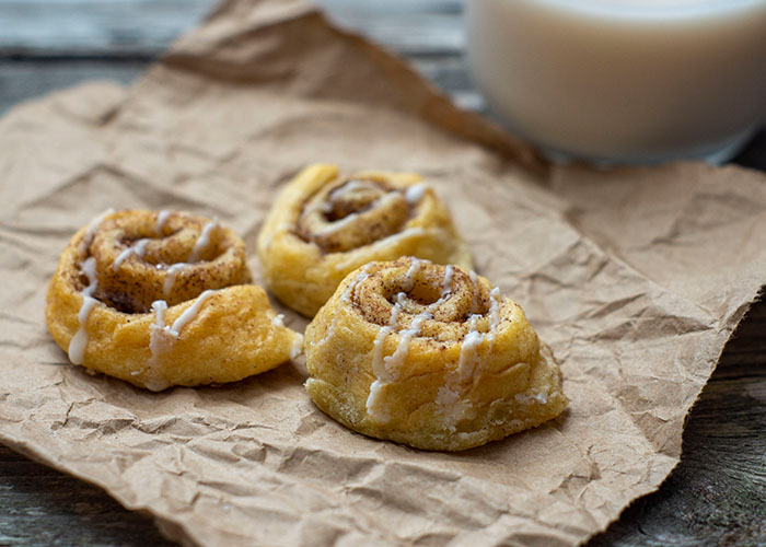 Three mini cinnamon crescents on a piece of brown paper with a glass of milk behind all on a wooden surface