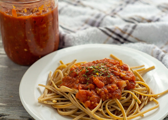 Spaghetti with homemade pasta sauce on a round white plate with a glass jar of pasta sauce behind next to a white and brown towel all on a wooden surface