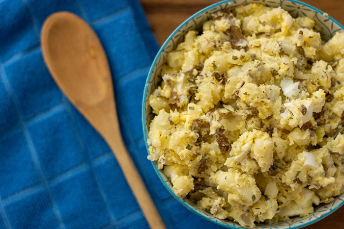 Homemade potato salad in a blue bowl next to a blue towel and wooden spoon