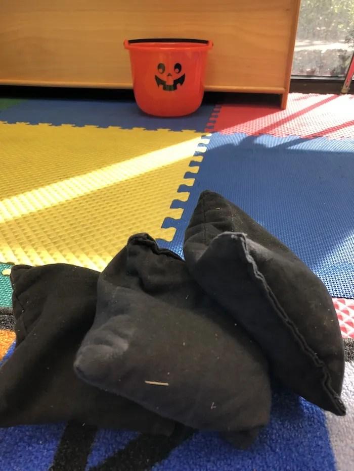 Orange Jack-O-Lantern bucket with black bean bags