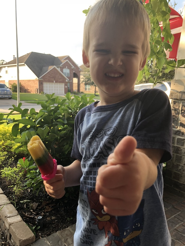 Young boy holding a tri-color ice pop in one hand and giving a thumbs-up