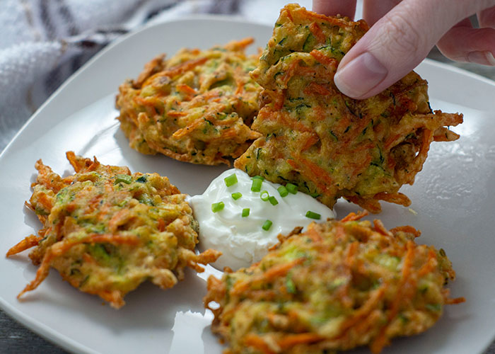 Woman's hand dipping a cooked vegetable fritter into sour cream in the middle of three other fritters on a square white plate with a white and brown towel behind all on a wooden surface