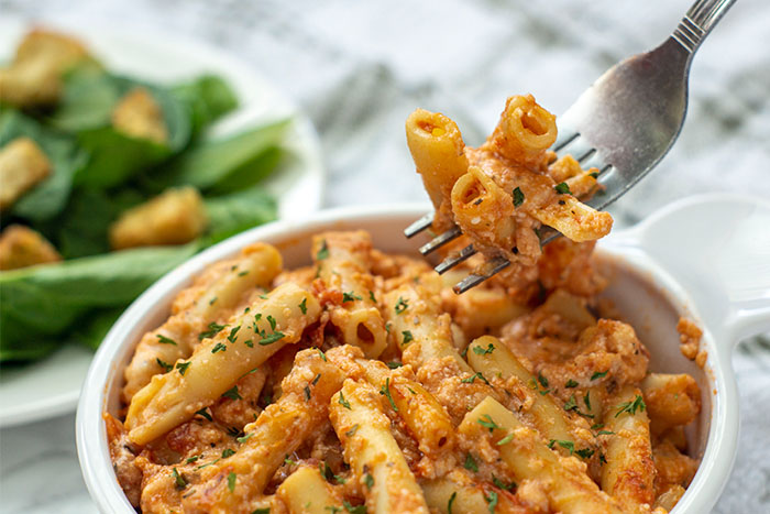 A bite of Baked Ziti in a white bowl being lifted by a fork (horizontal)