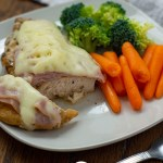 Cut piece of chicken cordon bleu with fresh carrots and broccoli on a square white plate with a stainless steel fork in front and a white and brown towel behind all on a wooden surface (vertical with title overlay)