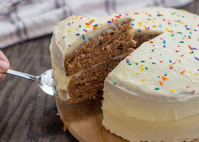 Serving spoon holding up a piece out of a double-layer chocolate cake with cream cheese frosting and rainbow sprinkles on a round bamboo platter with a white and brown towel behind all on a wooden surface