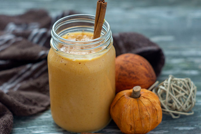 Pumpkin pie smoothie in a large mason jar with a stick of cinnamon sticking out next to fall decorations and a brown towel on a wooden surface