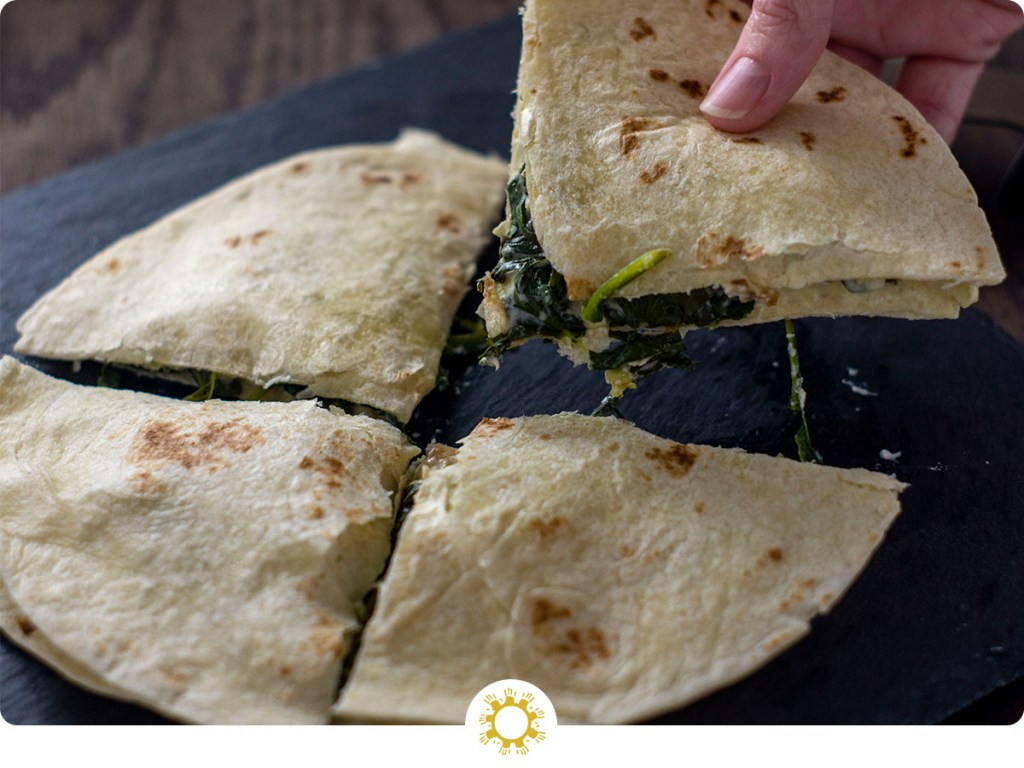 Spinach artichoke quesadilla cut into quarters with a woman's hand holding one piece up over a slate board on a wooden surface (with logo overlay)