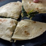 Spinach artichoke quesadilla cut into quarters with a woman's hand holding one piece up over a slate board on a wooden surface (vertical with title overlay)