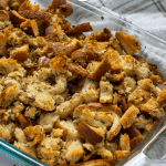Baked homemade stuffing in a glass baking dish on top of a white and brown towel all on a white surface (with title overlay)