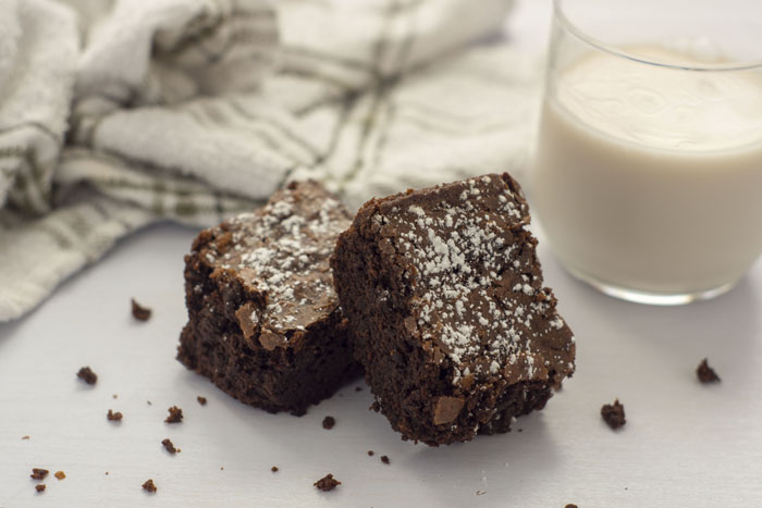 One brownie leaning on top of another brownie surrounded by brownie bits next to a glass of milk all on a white surface