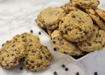 Chocolate chip cookies piled in a square white bowl with three cookies and a few chocolate chips to the side all on a white and grey marble surface