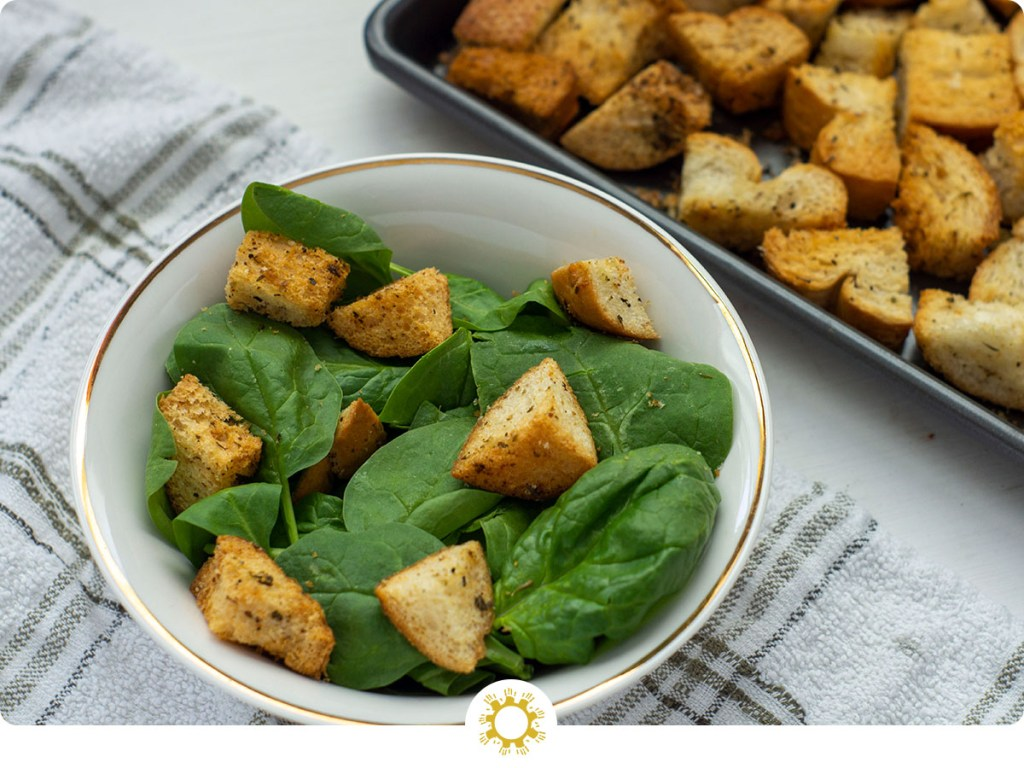 Italian-Style croutons on top of spinach leaves in a white bowl on top of a white and brown towel next to a metal baking sheet (with logo overlay)