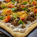 Baked taco pizza on a baking stone on a wooden surface (vertical with simple overlay)